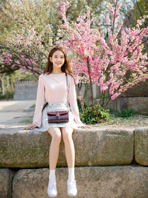 Một cô gái mặc váy dễ thương trên phông nền hoa thật xinh xắn